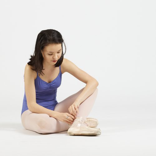 ballet dancer tying pointe shoe